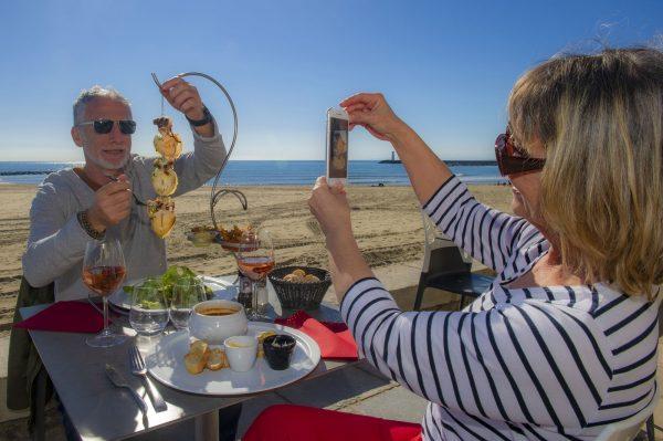 couple de jeuniors, quincados, en train de manger au restaurant, et de se prendre en photo avec la plage et la mer juste derrière eux au Cap d'Agde