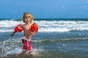 Petit garçon qui joue dans l'eau à la mer