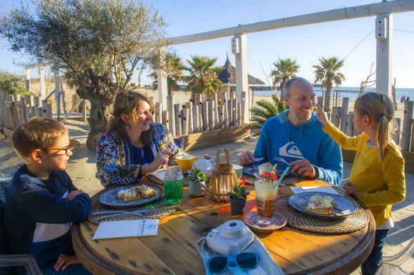 Famille avec deux enfants, en train de manger au restaurant, en train de rigoler, avec la plage et la mer juste derrière eux au Cap d'Agde