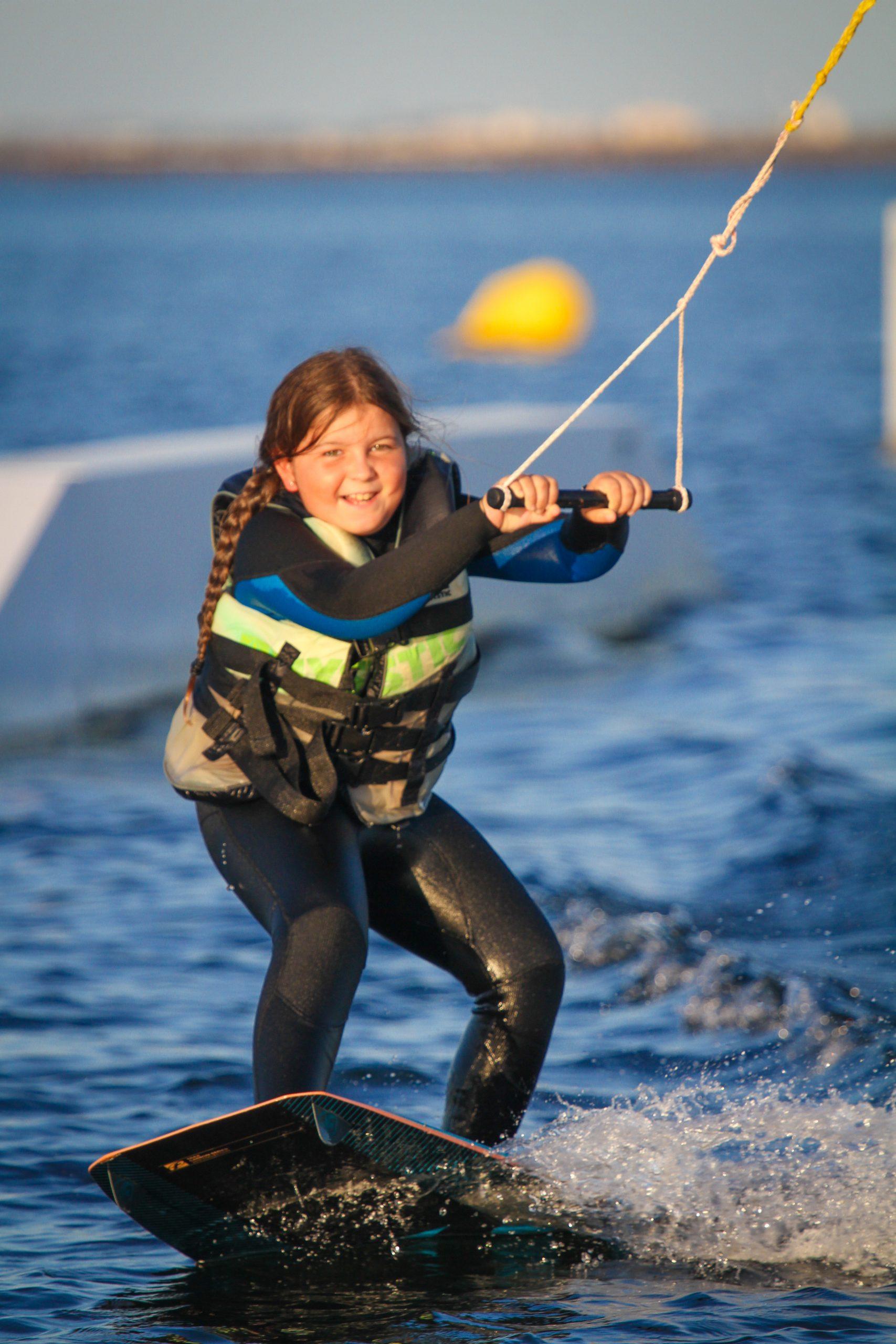Petite fille en wakeboard sur un Téléski nautique sur l'étang de Thau avec Kithau