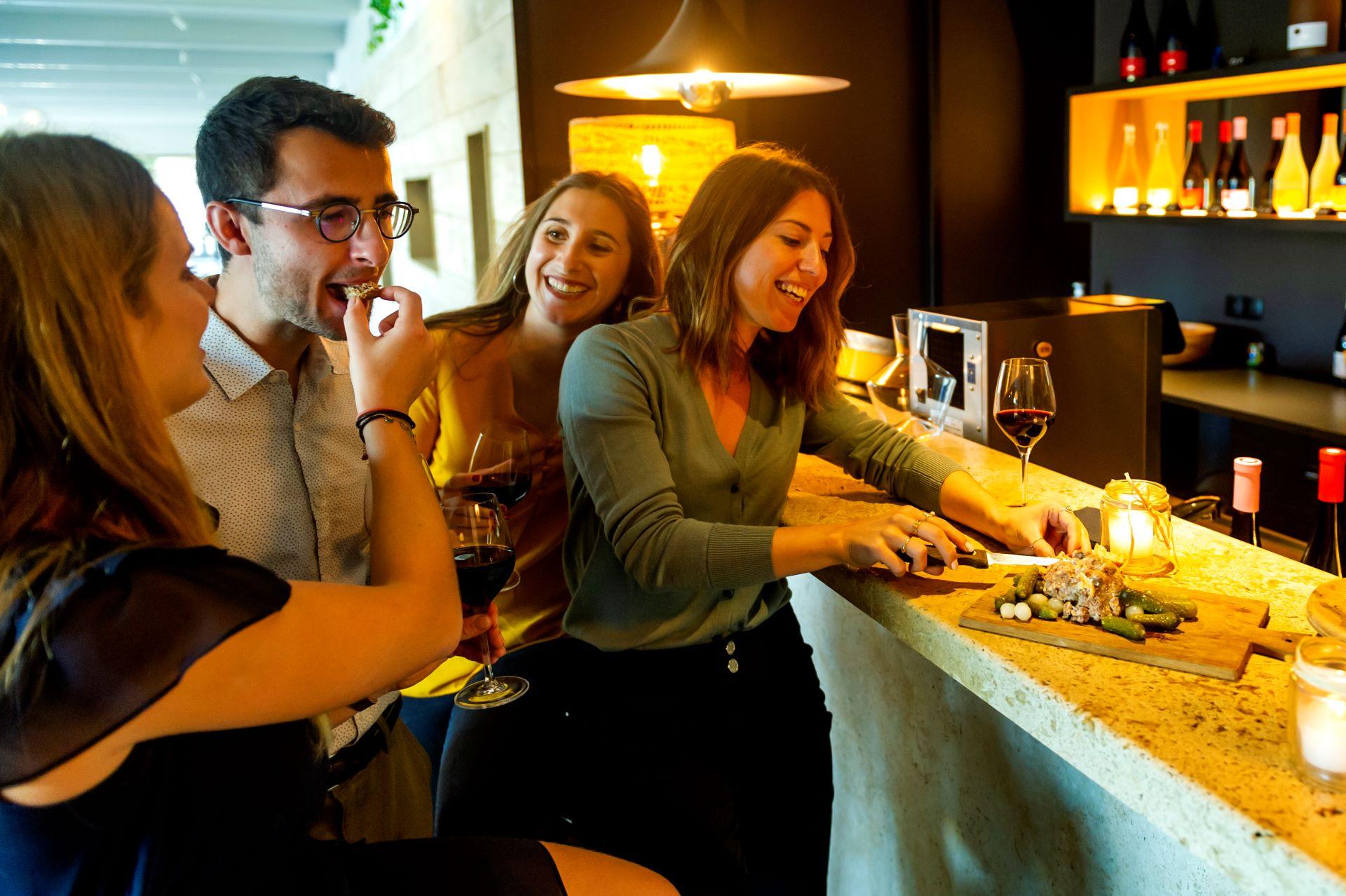 Groupe de jeunes amis en train de déguster une terrine de pâté avec des cornichon et du vin rouge