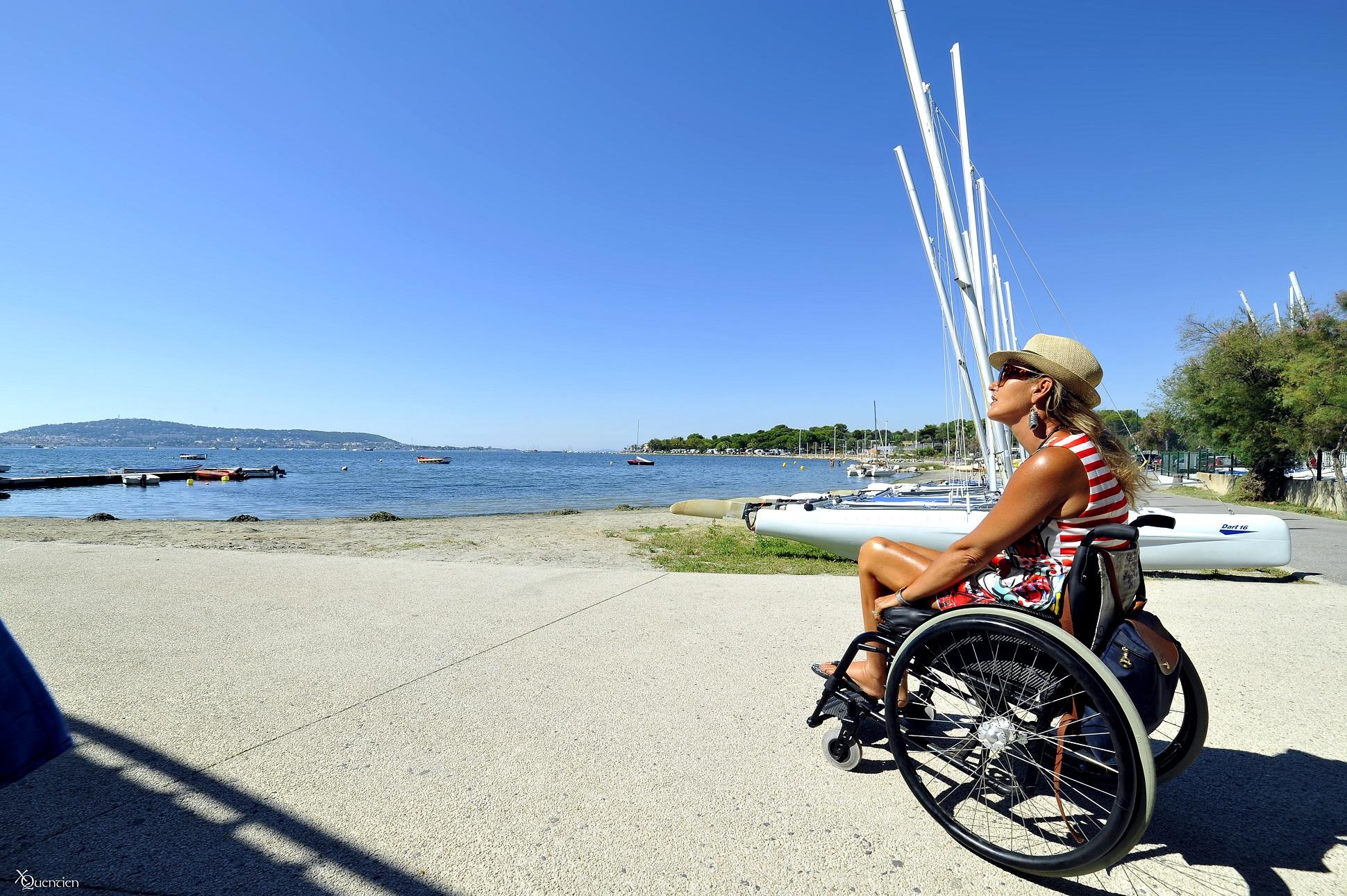 Une personne en fauteuil chemine vers les bateaux de Manureva