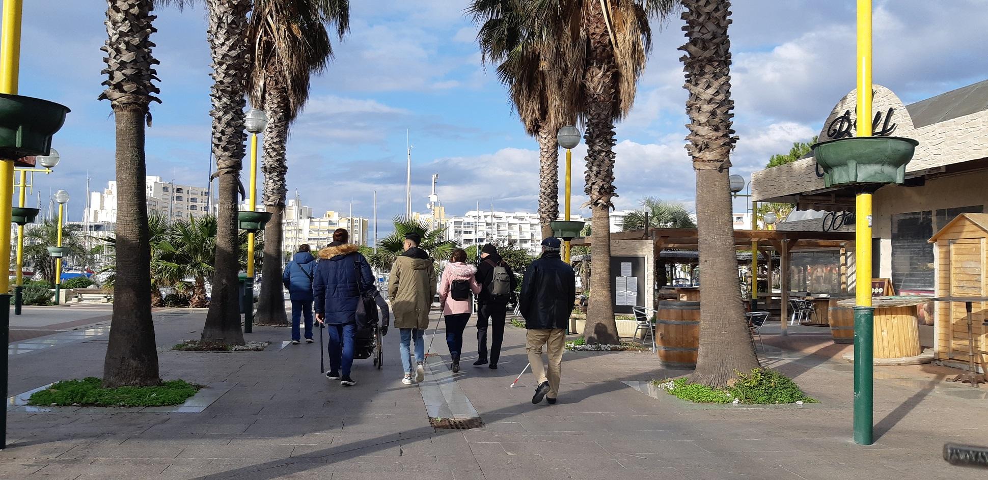Un groupe de personnes en situation de handicap visuel et moteur se promène sur le port de Carnon
