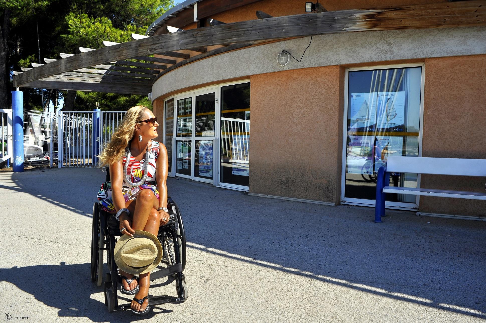 Une jeune femme en fauteuil roulant est devant l'entrée du centre nautique Manureva