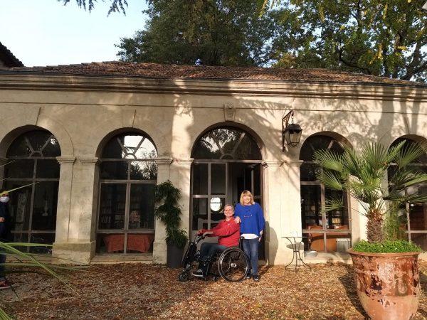 Couple avec un handicap moteur devant un domaine viticole