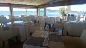 Tables dans un restaurant devant l'étang de Thau avec la colline de Sète en arrière-plan