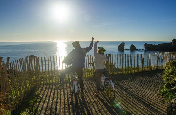 Un couple de quincas se balade à vélo sur les falaises de la Plage de la Conque au Cap d'Agde