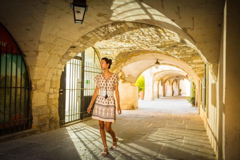 Jeune femme qui déambule sous un porche dans le centre historique de Lunel