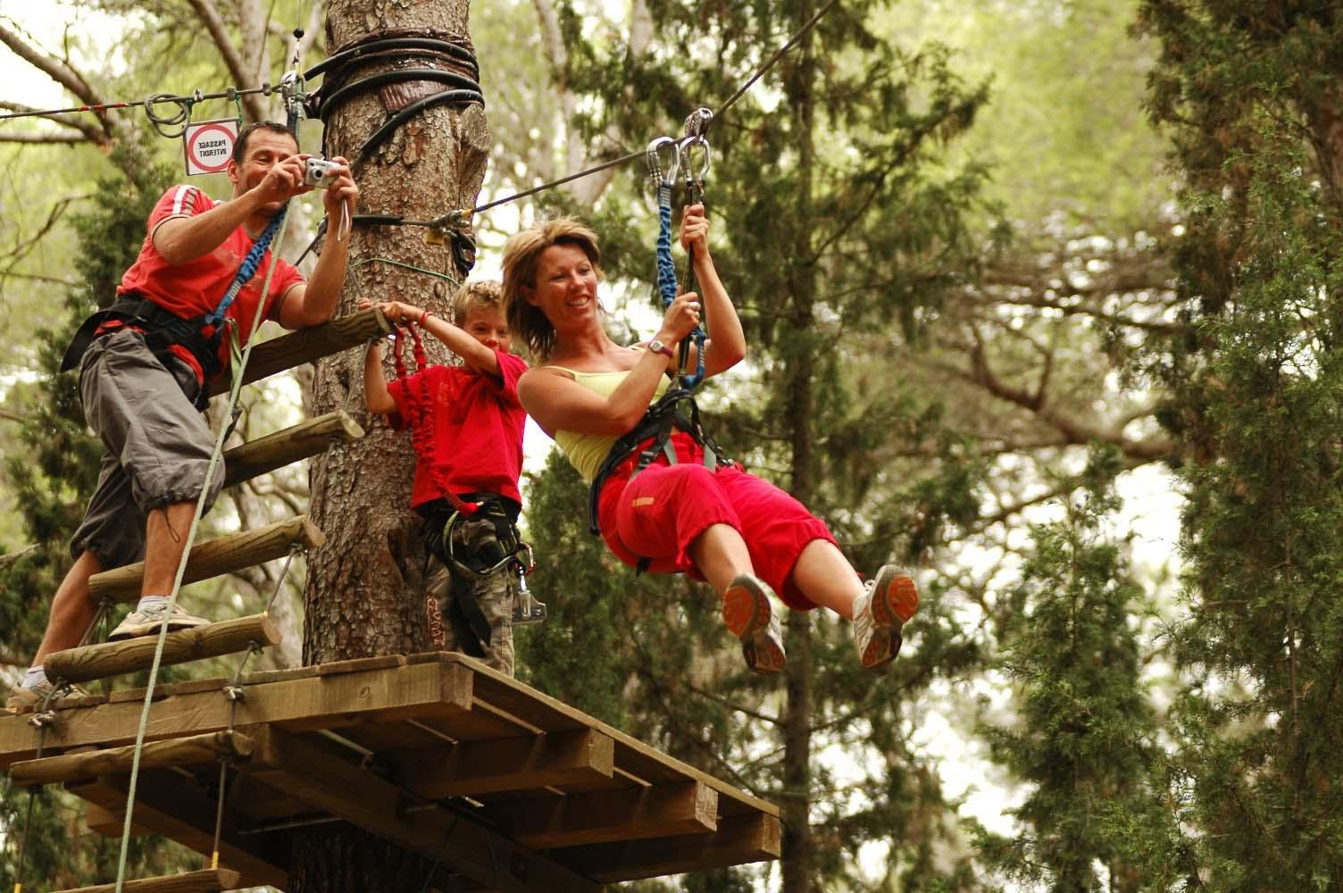 Jeune femme sur un Parcours dans les arbres à la Forêt d'acrobates à Bessilles